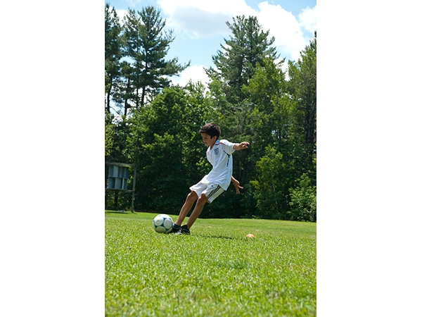 Young male camper playing soccer at camp