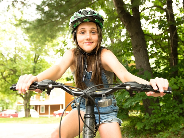 Girl riding a bicycle at camp during the summer