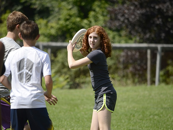 Kids and teens playing frisbee at summer camp