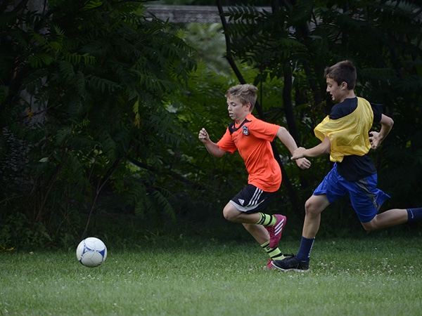 Kids running and playing soccer at summer camp