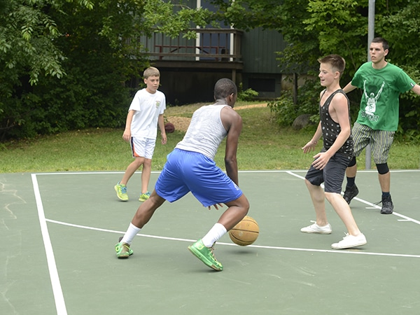 Counselors and teen campers playing basketball on the court at summer camp