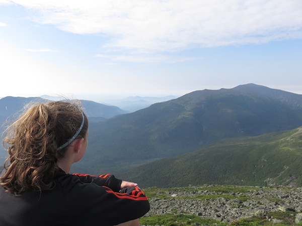 Girl sitting onsummit of White Mountains in New Hampshire
