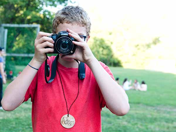 Adam in photography class taking photos at summer camp