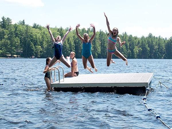 Happy girls jumping off dock into lake in the summer