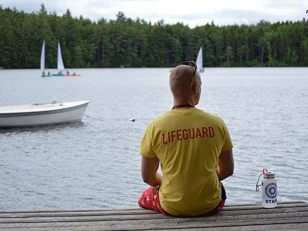 Camp counselor lifeguarding campers at summer camp in New Hampshire