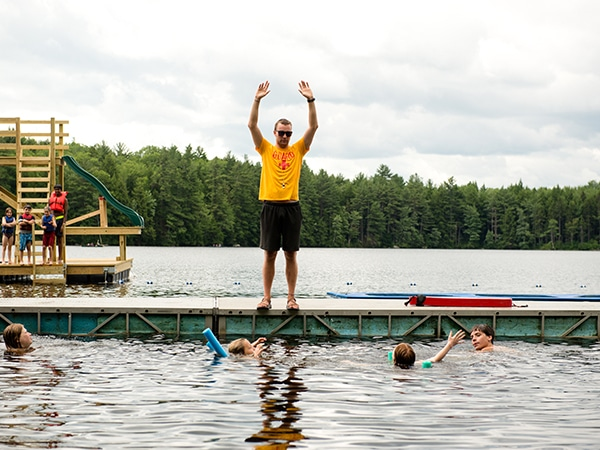 Summer camp lifeguard instructor teaching swimming lesson in the lake