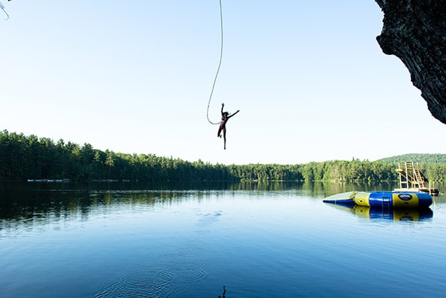 Camper jumping off rope swing into lake during the summer