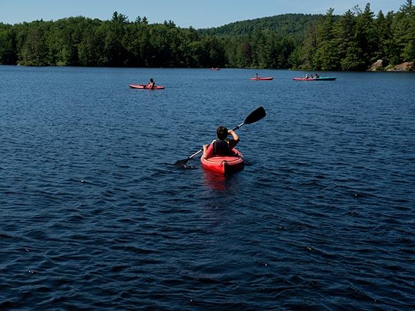 Windsor Mountain summer camper in kayaking on the lake