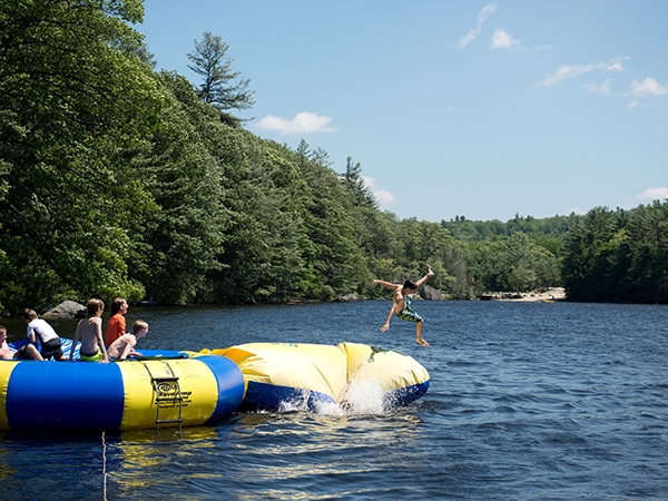 Boy jumping off water trampoline into lake