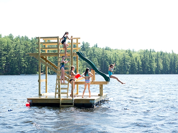 Girls jumping off water slide into New Hampshire lake