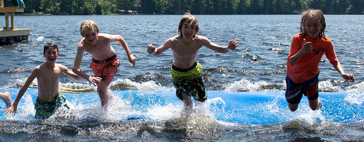 Windsor Mountain campers jumping off the water mat into the cool lake on a warm summer day in New Hampshire