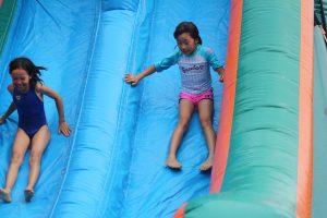 Girls sliding down waterslide at summer camp